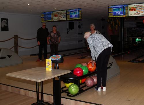 Lenie v.d. Vloet zoekt een bal uit die niet te zwaar is. Op de achtergrond Marja, Frans en Ton die net gegoid hebben