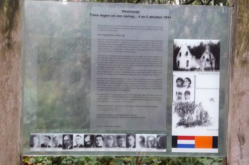 Het bord met daarop het verhaal en de namen met foto's van de slachtoffers