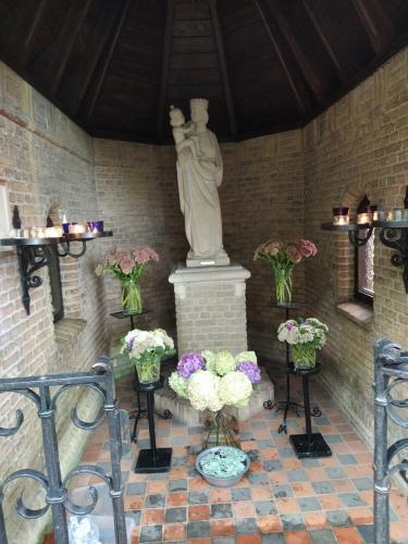 Het interieur van het mooie kapelletje waar de vudb-stop was met mooie bloemen, kaarsjes en een mooi wit Mariabeeld.