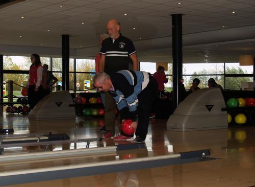 Eric gooit een bowlingbal terwijl Pieter hem in de gaten houdt