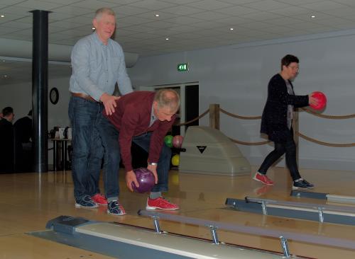 Herman helpt Wim zodat hij een goede score kan halen tijdens de bowlingmiddag. Op de achtergrond staat Marina klaar voor haar beurt