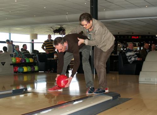 Anneke helpt Jac zodat hij een goede score kan halen tijdens deze bowlingmiddag