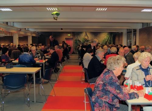 Een overzicht van de zaal met deelnemers aan de Bridgedrive