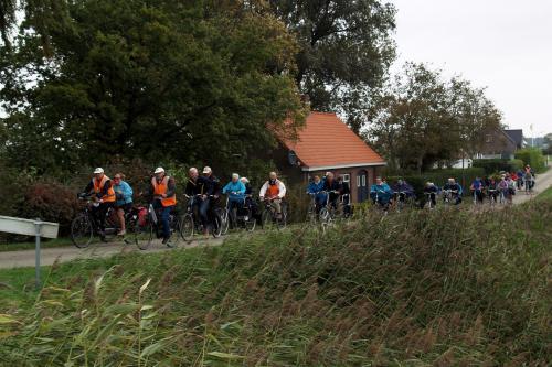 Een groot peloton rijdt tegen de wind in tijdens de laatste tandemtocht van Piet Brocatus