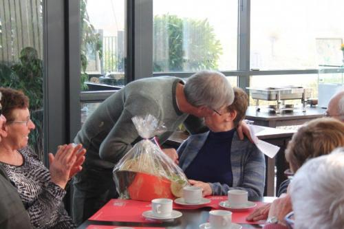 Johan reikt een fruitmand uit aan Addy vergezeld van enkele felicitatiekussen