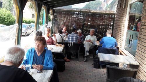 Enkele deelnemers zitten voor de lunch op het overdekte terras aan de zijkand van het cafe