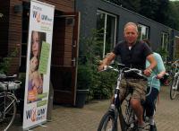 Johan rijdt met Esmeralda op de tandem langs een banner van ''Wouw Doet''