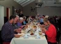 De deelnemers genieten van de lekkere koffietafel