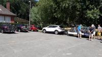 Een aantal auto's en aanhanger met daarop de tandems en fietsen bij het startadres het parochiecentrum in Essen