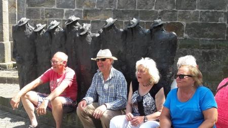 enkele deelnemers bij het bekende beeldje van mannen met hoed in Ootmarsum