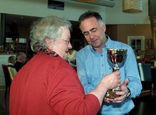 Eric overhandigd Jaantje de beker voor haar overwinning in het jaarklassement bij de B-categorie