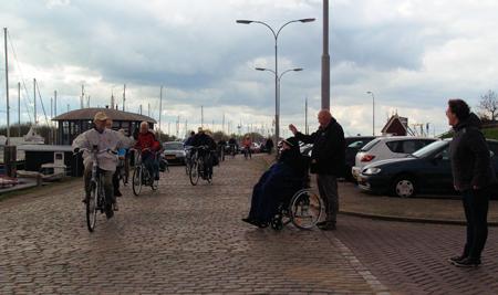 Jo, goed ingepakt tegen de kou, zwaait de deelnemers aan zijn tocht in Tholen uit