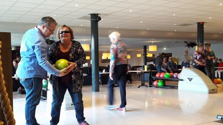 John helpt Ria tijdens het bowlen