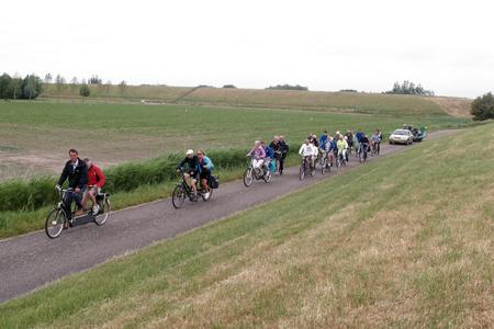 De deelnemers aan de Kiwanistocht rijden even een stukje onderaan de dijk waar wat minder wind staat