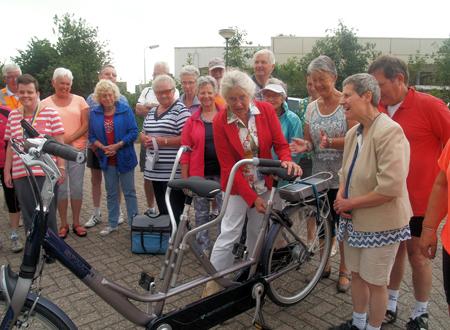 Juul doet onder het toeziend oog van de deelnemers de fiets van het slot